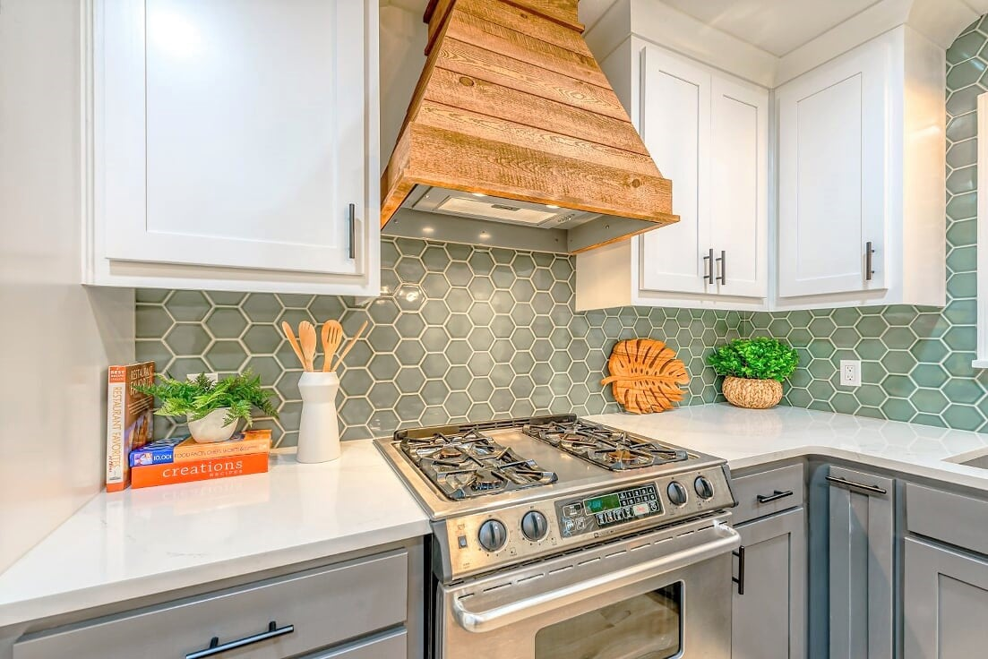 Every kitchen should have a fun focal point and this rustic, wood venthood is some awesome eye candy and so is that sage hex backsplash.